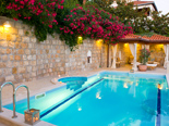 The swimming pool sits on top of the upper terrace and is surrounded by colourful garden with palm trees, oleanders and cypress trees.