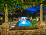 View on the pool area from the courtyard of this Dubrovnik holiday villa by night